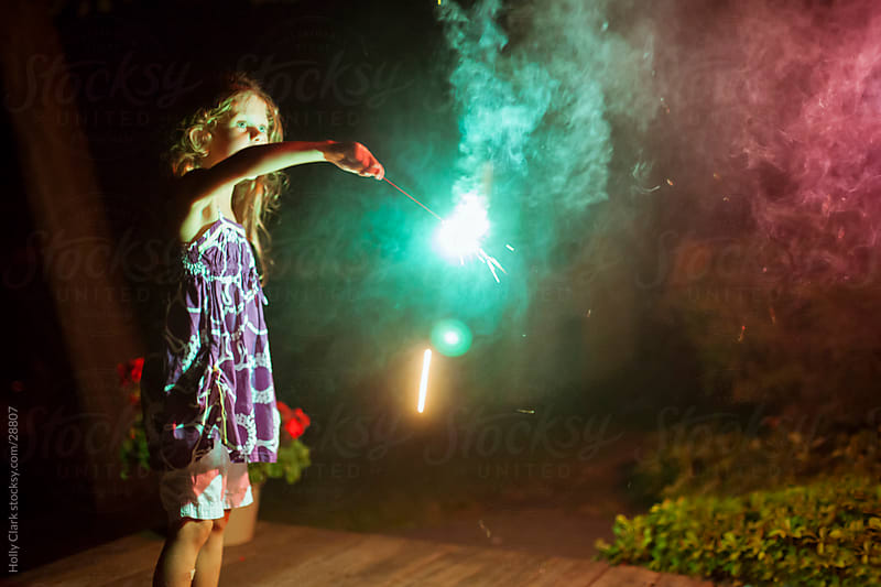 Young Girl Playing with Sparkler on the Fourth of July by Holly Clark for Stocksy United