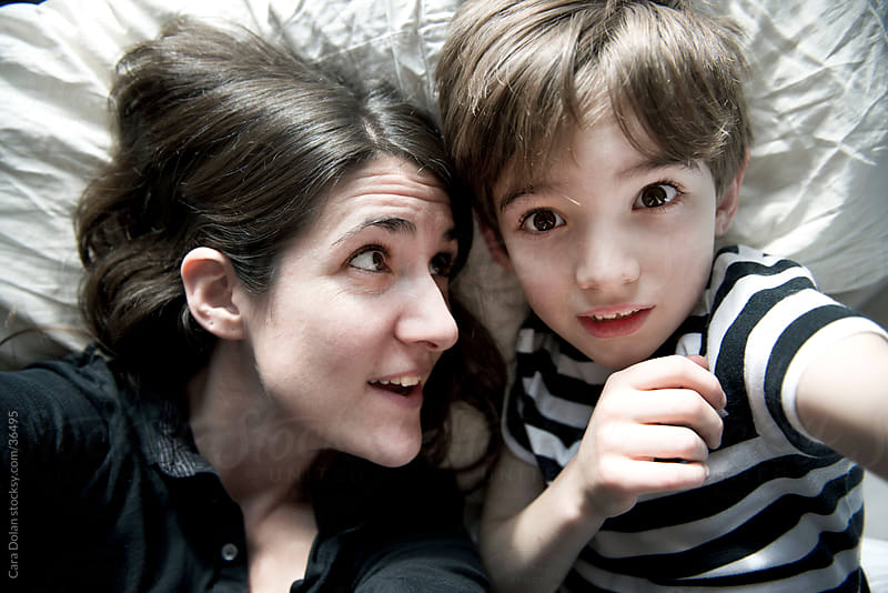Mother and son take self portrait on bed by Cara Dolan for Stocksy United