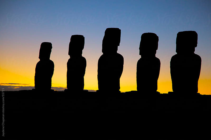 The breaking of Dawn behind five Moai stone statues, Easter Island, Chile by Jaydene Chapman for Stocksy United