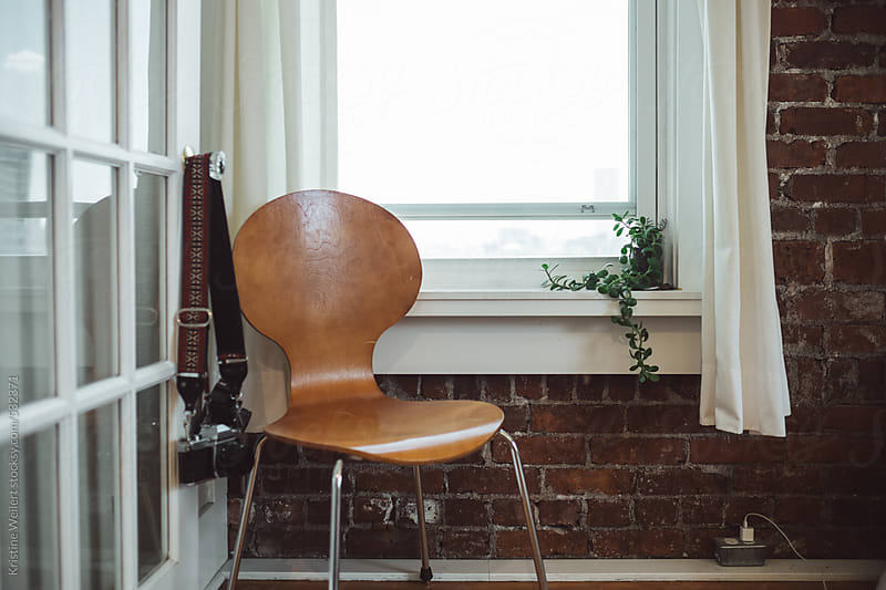 A wooden chair sitting next to a window and a brick wall by Kristine Weilert for Stocksy United