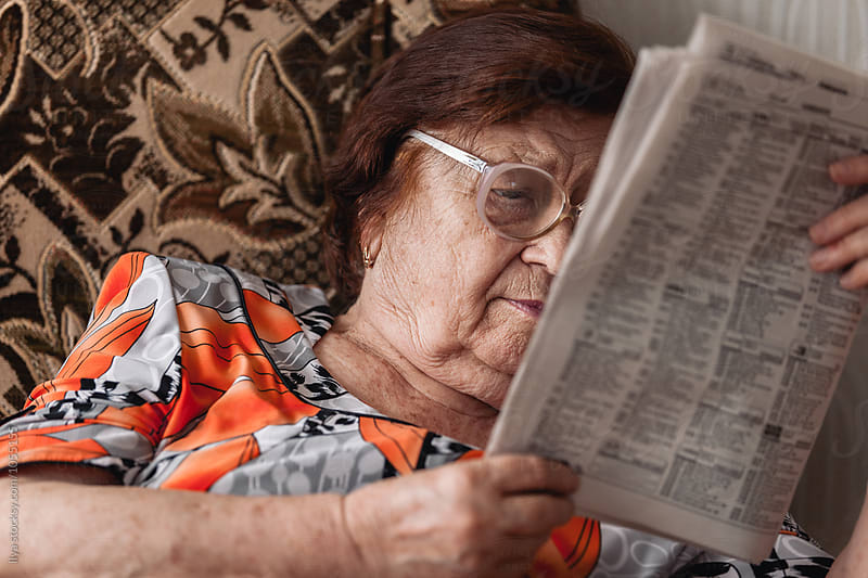 Old woman reading newspaper sitting in chair by Ilya for Stocksy United