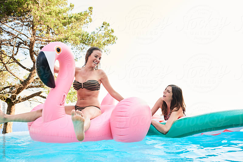 Two cheerful girlfriends having fun on inflatables in pool by Guille Faingold for Stocksy United