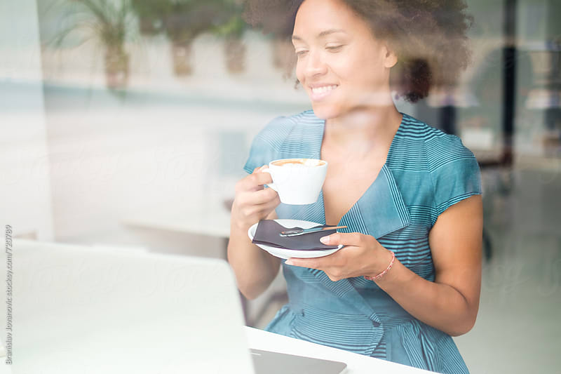 Beautiful Smiling Woman Drinking Coffee and Looking at Computer by Branislav Jovanović for Stocksy United