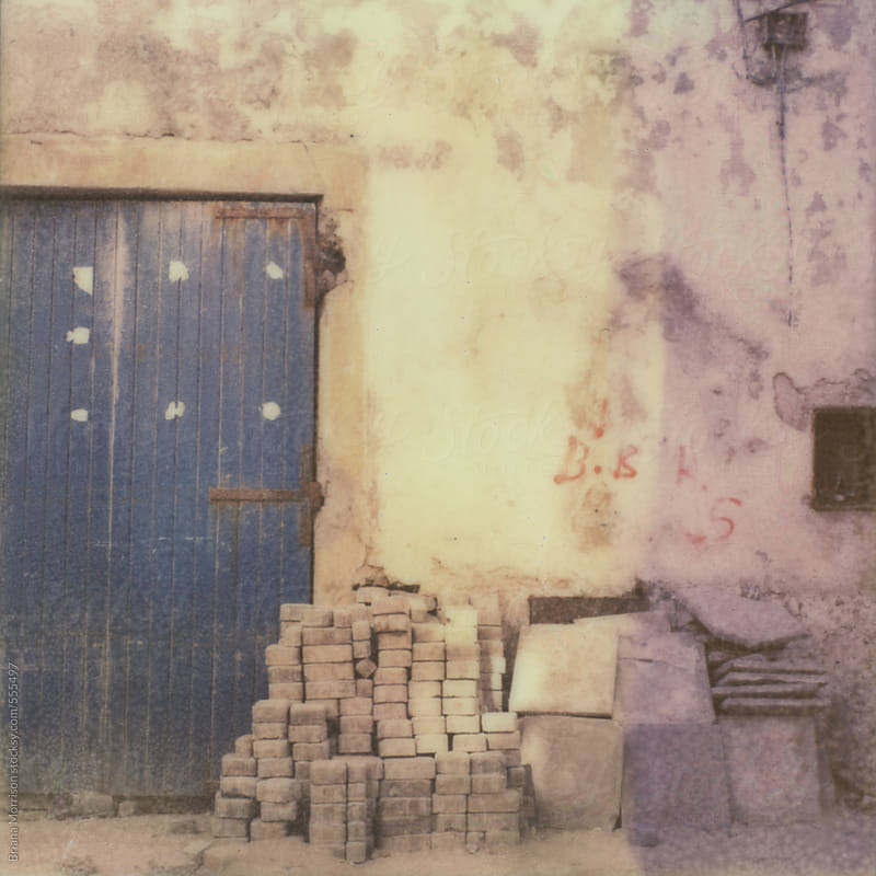 A Blue Door and a Pile of Old Bricks Stacked Next To an Old Moroccan Building by Briana Morrison for Stocksy United
