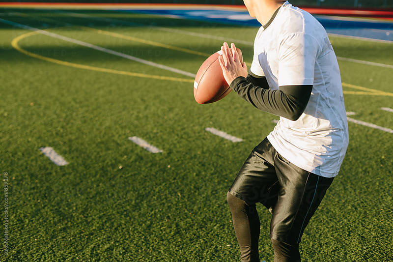 Athletic Man Preparing To Throw Football On Artificial Turf Field by Luke Mattson for Stocksy United