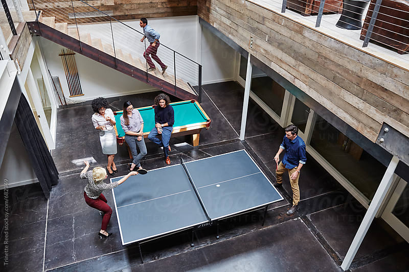 Group portrait of millennials playing ping pong at work by Trinette Reed for Stocksy United