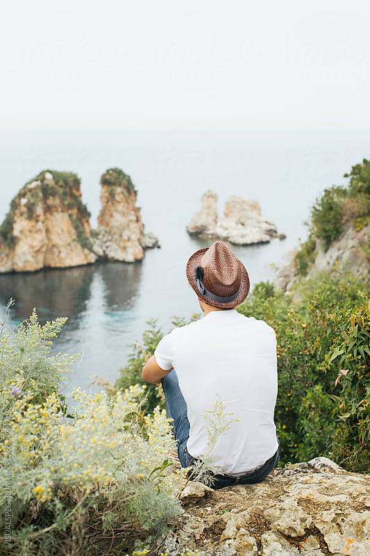 Young Man Wearing Brown Straw Hat Sitting by Ocean and Looking at Sea by VISUALSPECTRUM for Stocksy United