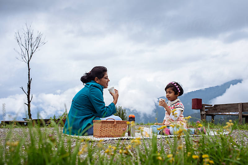 Mother and daughter drinking coffee at a picnic in the hills by Saptak Ganguly for Stocksy United