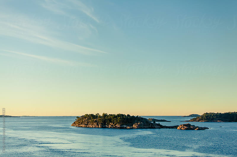 Small islands in the ocean of the Norwegian coast during sunrise in the summer by Cindy Prins for Stocksy United