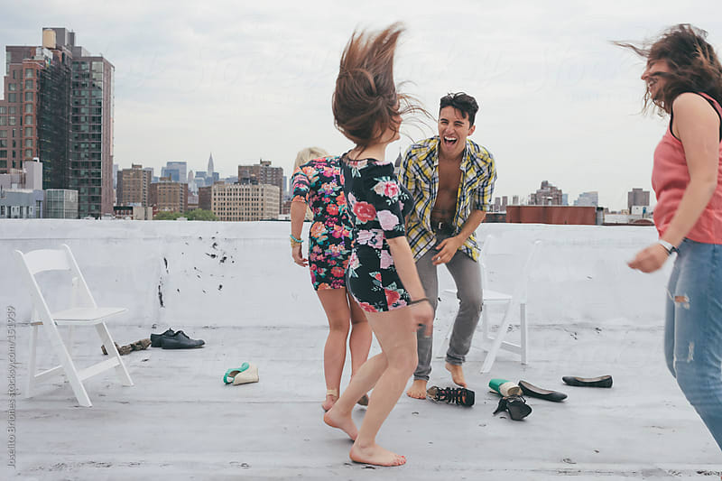Friends Having Fun and Dancing on a New York Rooftop by Joselito Briones for Stocksy United