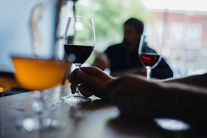 Man holds the stem of his wine glass at a bar by Cara Dolan for Stocksy United
