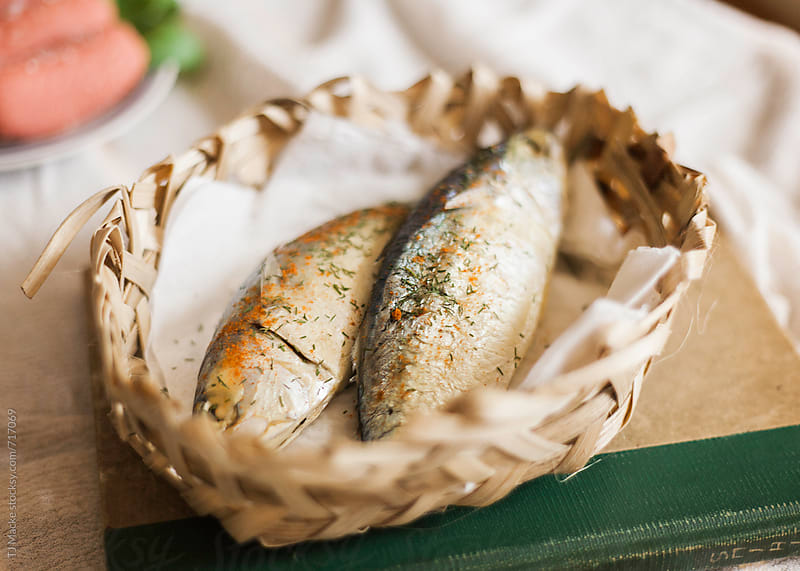 Cooked fish sitting in a basket on the table  by TJ Macke for Stocksy United