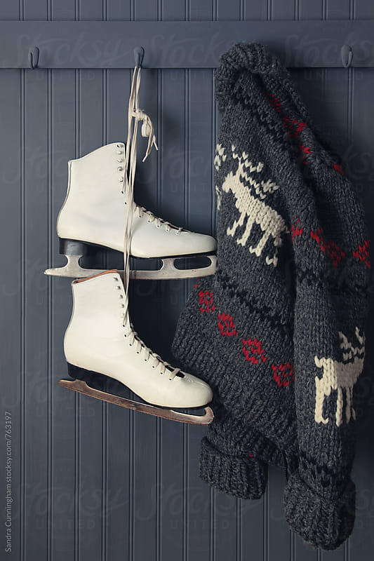 Old ice skates and sweater hanging on hooks by Sandra Cunningham for Stocksy United