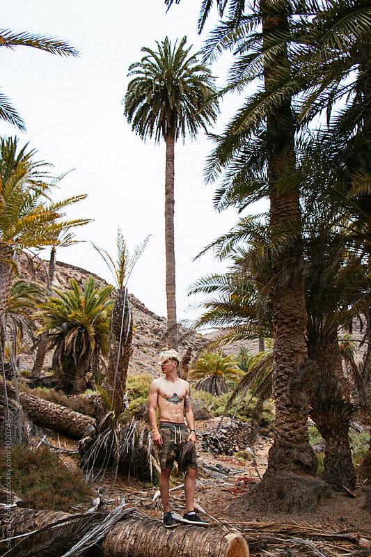 Portrait of young man in a palm grove by Susana Ramírez for Stocksy United