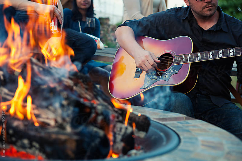 Party: Man Playing Guitar By Fire Pit by Sean Locke for Stocksy United