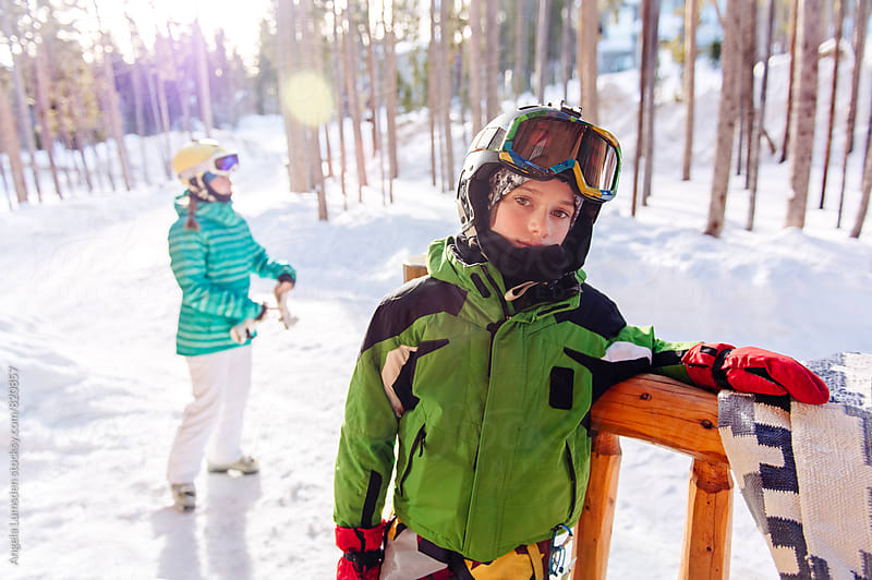 Boy bundled in ski clothes waits impatiently to get going skiing by Angela Lumsden for Stocksy United