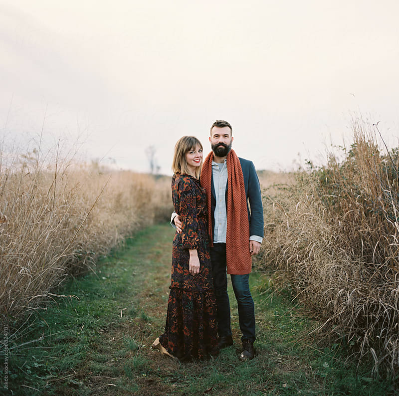 Beautiful and stylish couple embracing by a field  by Jakob for Stocksy United