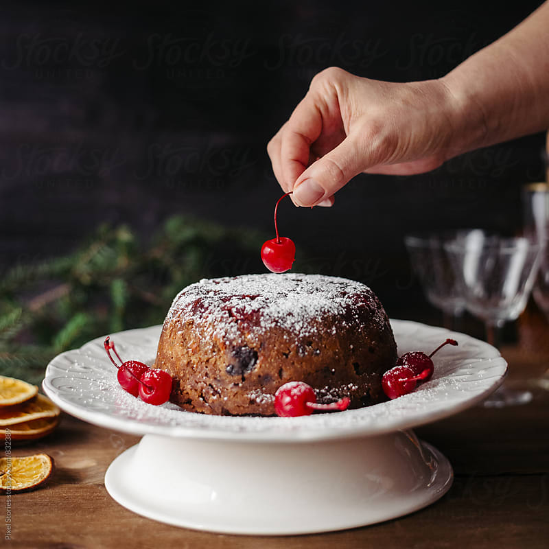 Woman placing cocktail cherry on Christmas pudding by Pixel Stories for Stocksy United