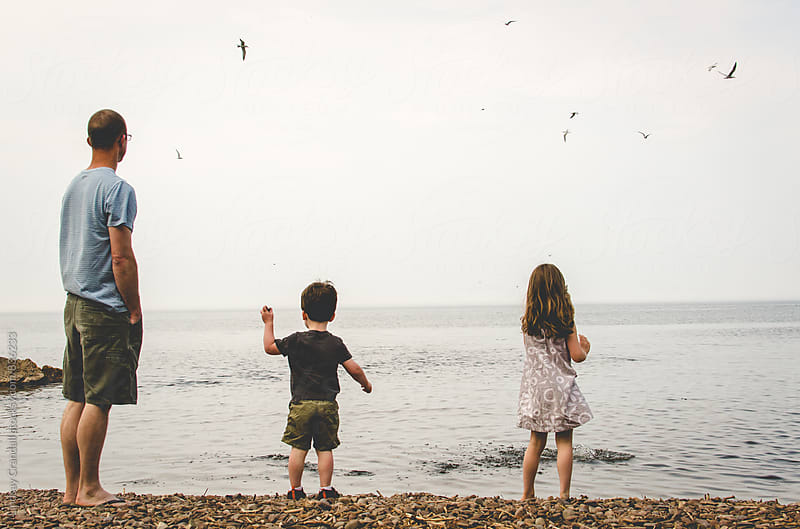 Father with children throwing rocks into the sea by Lindsay Crandall for Stocksy United