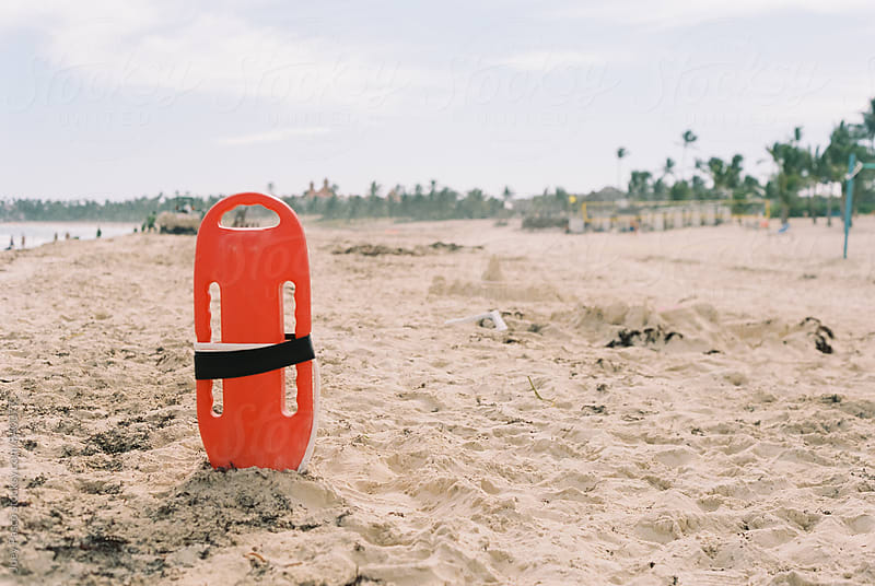 Orange lifeguard buoy on at white sand Caribbean beach by Joey Pasco for Stocksy United