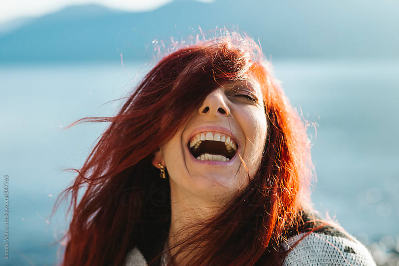 Happy woman outdoors during a winter day at lake by Simone Becchetti for Stocksy United