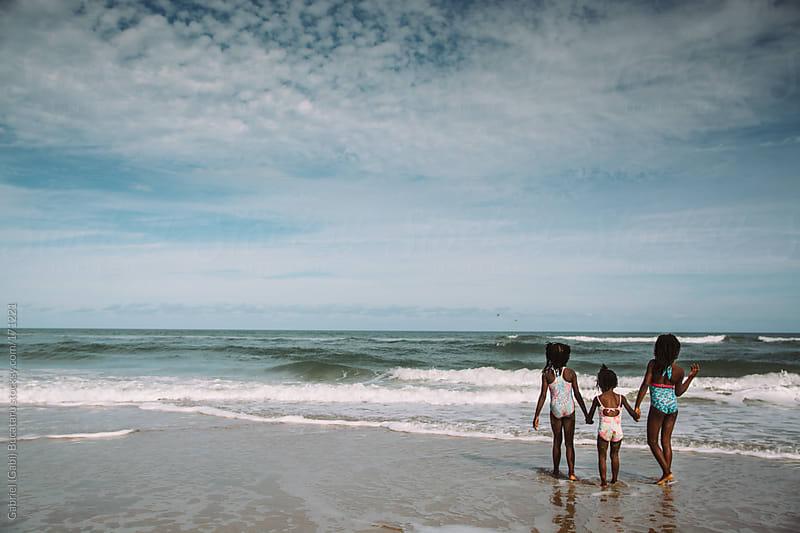 Three black girls by the sea by Gabriel (Gabi) Bucataru for Stocksy United