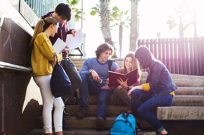 Group of teen friends studying on the street. by BONNINSTUDIO for Stocksy United