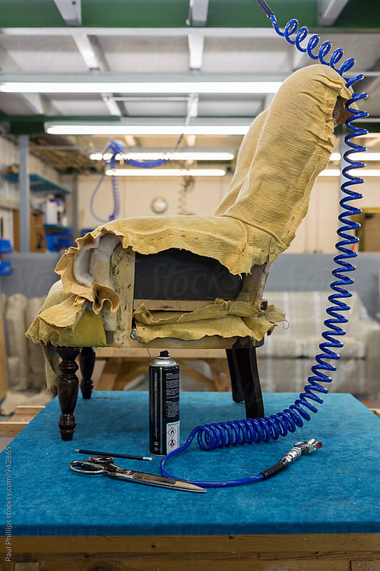 Old chair in the process of being re-upholstered standing in a workshop. by Paul Phillips for Stocksy United