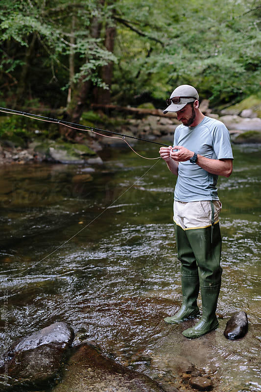 Man fly-fishing in clear river tying fly to line by Matthew Spaulding for Stocksy United