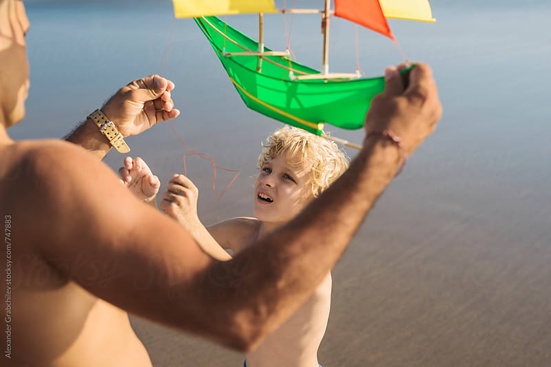 Adult Man and child flying a kite at the beach by Alexander Grabchilev for Stocksy United
