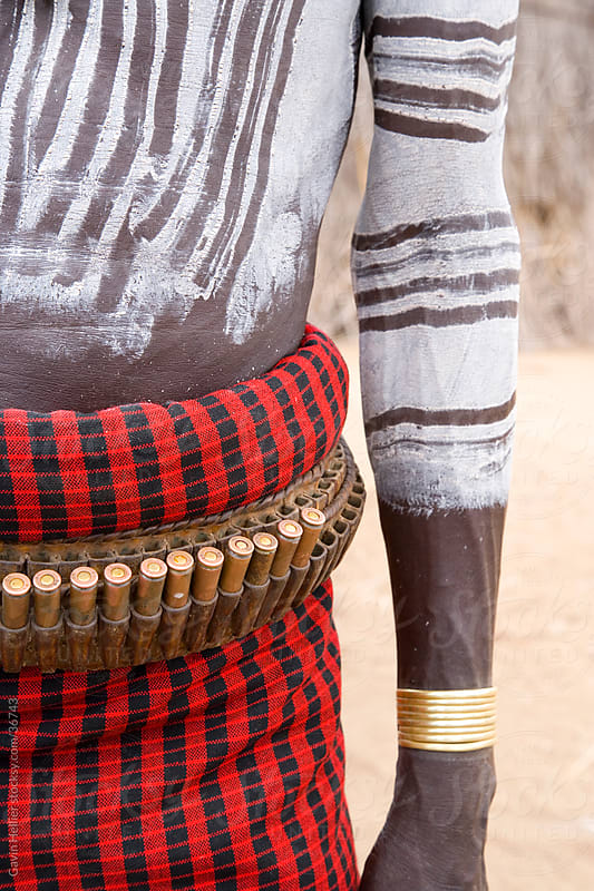 Karo Tribesman wearing a belt of bullets,  Lower Omo Valley, Ethiopia, Africa by Gavin Hellier for Stocksy United