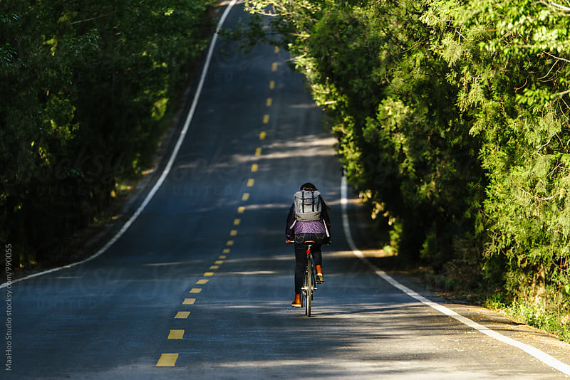 Young girl riding bicycle on a road by Maa Hoo for Stocksy United