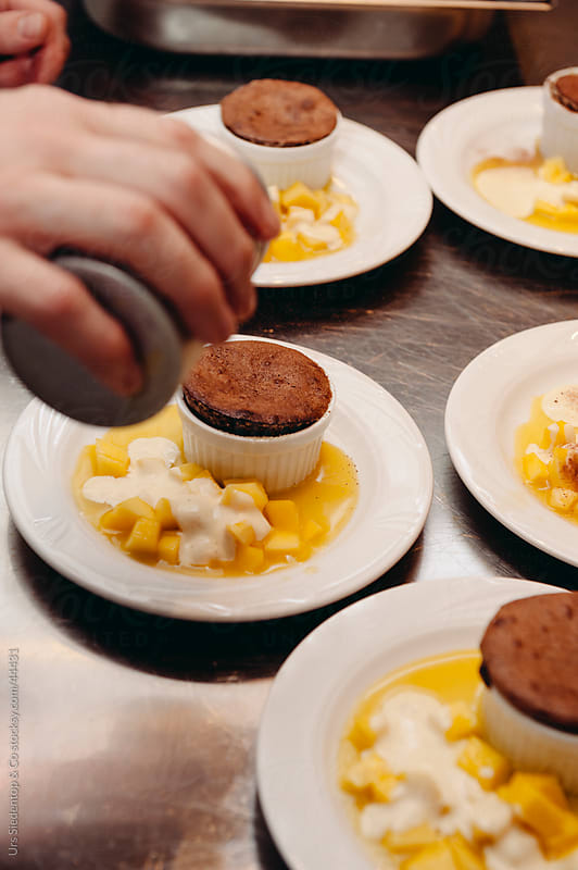 Hot brownie chocolate cake dessert with mango fruits and vanilla cream by Urs Siedentop & Co for Stocksy United