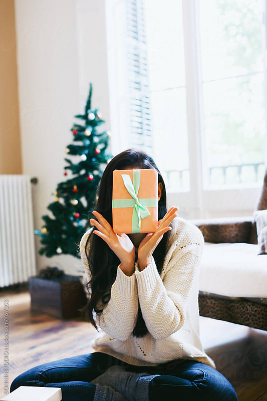Woman hiding her face with a Christmas gift. by BONNINSTUDIO for Stocksy United