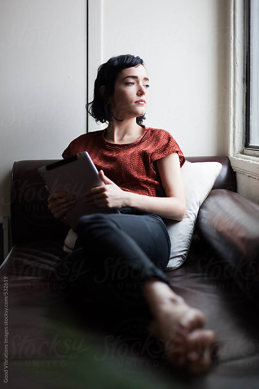 Brunette on the sofa reading a digital tablet by Good Vibrations Images for Stocksy United