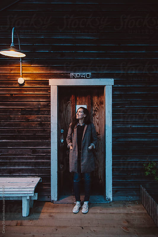 Evening portrait of woman standing in doorway by Carey Shaw for Stocksy United