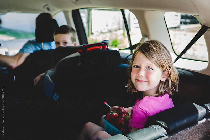 Smiling girl in backseat of minivan with family by Lindsay Crandall for Stocksy United
