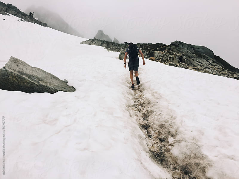 Male Hiker on a Snowy Mountain Trail in Washington by michelle edmonds for Stocksy United