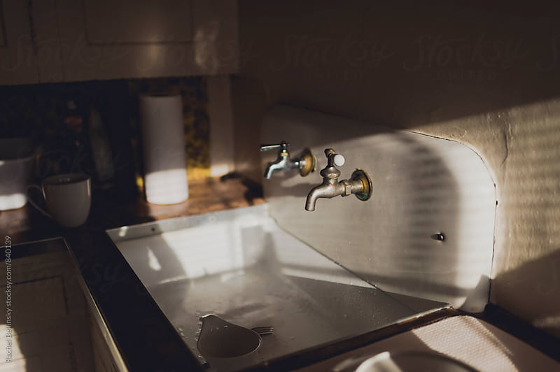 A vintage sink in an old apartment in shadowy morning light by Rachel Bellinsky for Stocksy United