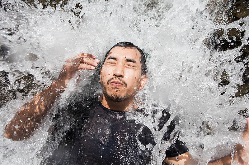 Young asian man cooling off in a waterfall by Shikhar Bhattarai for Stocksy United