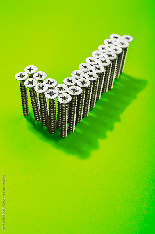 Check sing shaped with lot of screws on green background. Social media icon. by BONNINSTUDIO for Stocksy United