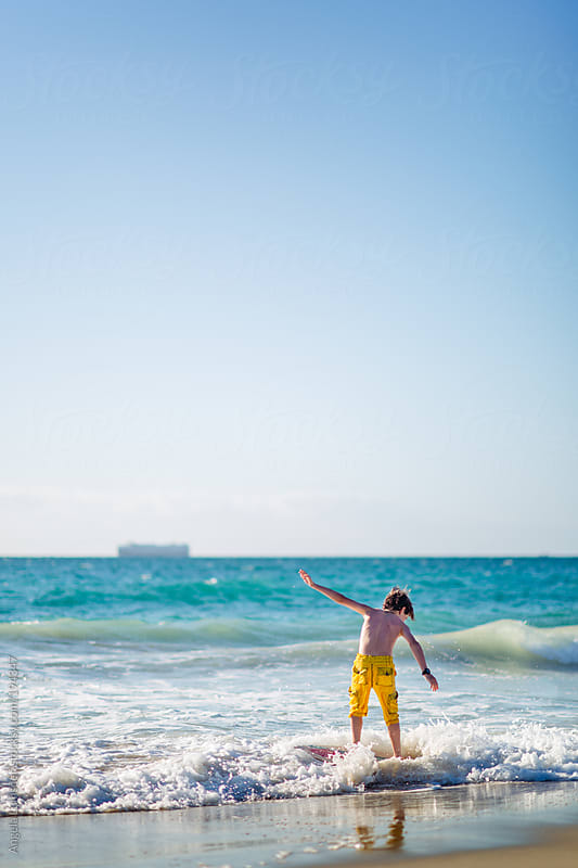 Boy catching a wave on a skim board at the beach by Angela Lumsden for Stocksy United