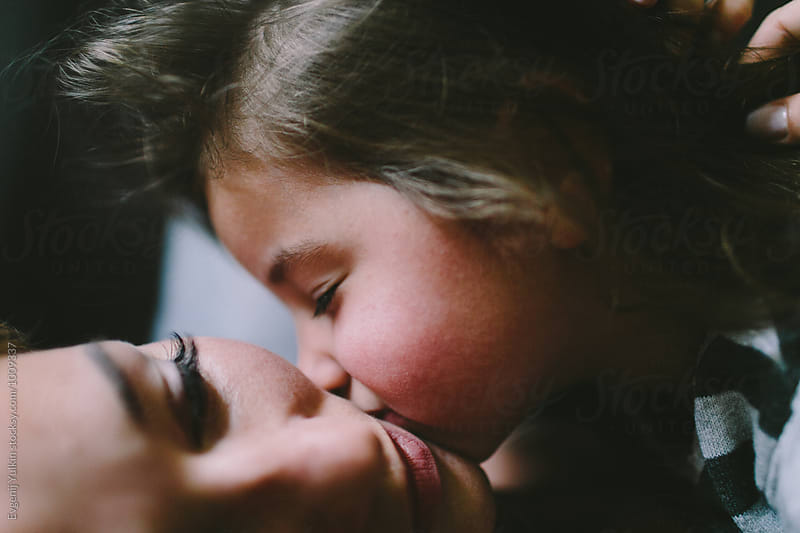 Daughter kissing her mother by Evgenij Yulkin for Stocksy United