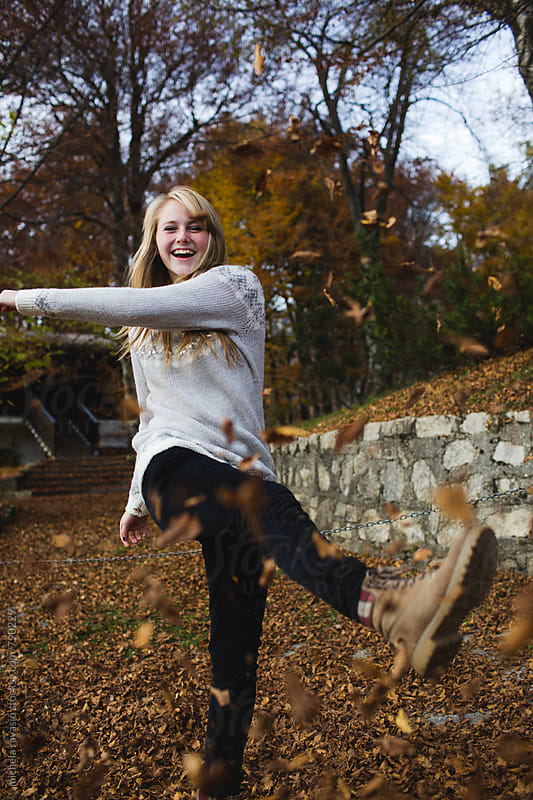 Girl having fun kicking the dry leaves by michela ravasio for Stocksy United