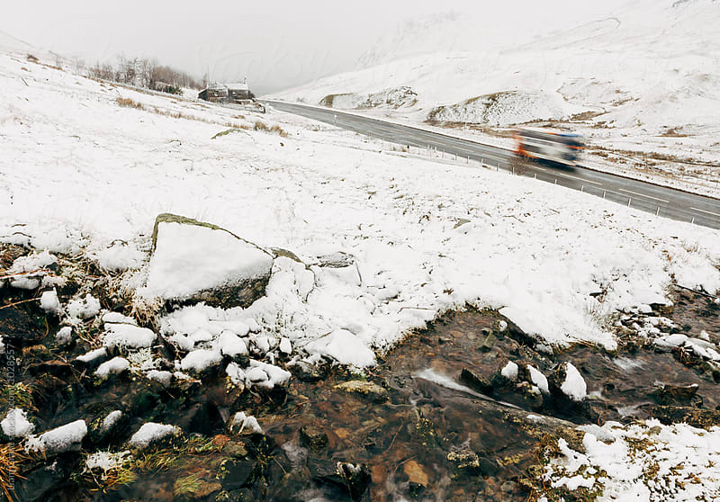 Public bus driving on a mountain road in snow. Cumbria, UK. by Liam Grant for Stocksy United