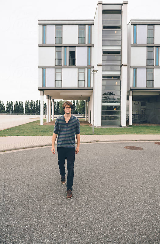 Man in front of modern architecture by Urs Siedentop & Co for Stocksy United