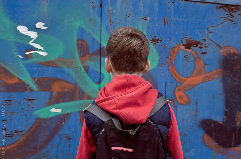 Boy from the back with schoolbag looking in graffiti on the wall by Marija Anicic for Stocksy United