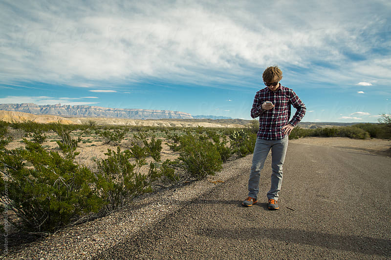 Man on side of the road in West Texas with cell phone by Dalton Campbell for Stocksy United