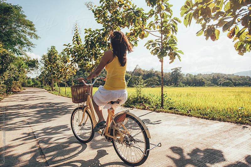 Happy Asian Woman Riding a Bike by Goldmund Lukic for Stocksy United