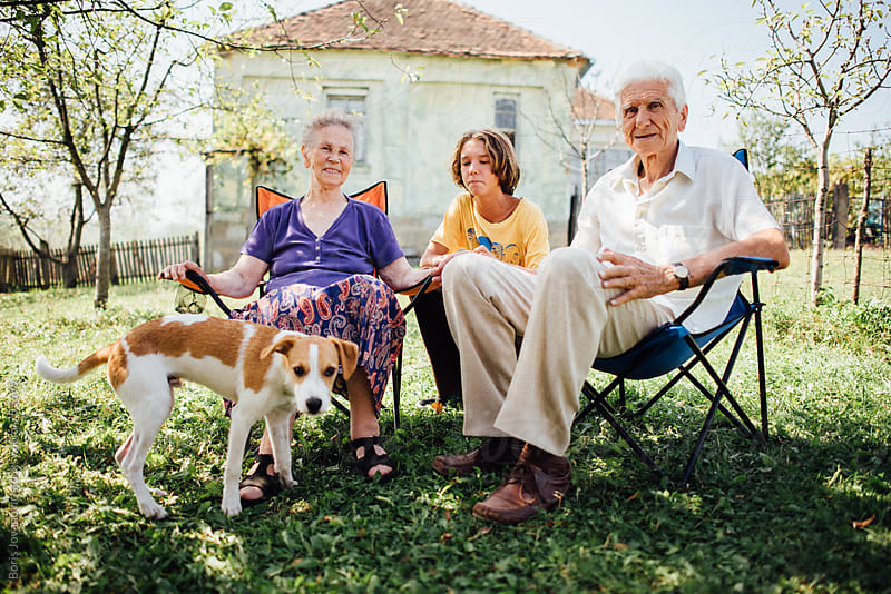 Grandparents and grandson enjoying a beautiful day out with their dog by Boris Jovanovic for Stocksy United